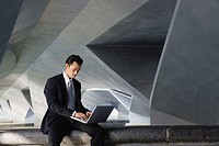 Businessman sitting on ledge, using laptop