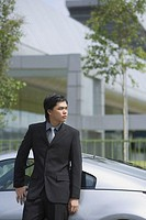 Businessman leaning on silver sports car, looking away