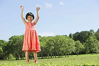 Girl in park, hands in the air, looking at camera