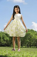 Girl wearing dress, standing in park, smiling at camera