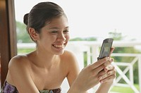 Woman using mobile phone, text messaging