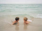Two boys (4-6) lying on sand, looking over shoulders out to sea