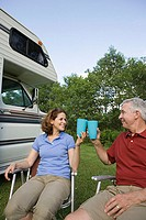 Couple toasting outside caravan