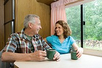 Couple drinking coffee in a caravan