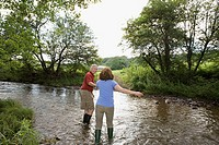 Mature couple crossing a stream