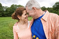 Smiling couple face to face in a field