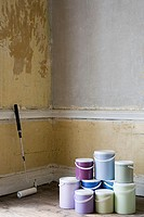 Paint roller and paint pots in room