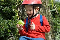 Boy in a bike helmet with an apple