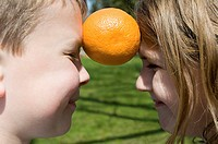Boy and girl with orange between them