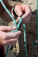 Rock climber knotting rope