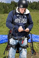 Male parachutist adjusting his equipment