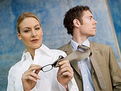 Business woman cleaning spectacles with man´s tie