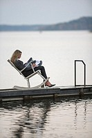 Businesswoman sitting in rocking chair on jetty, side view
