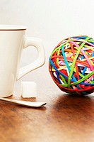 Coffee cup, sugar cube and colourful ball of rubber bands on table, close-up
