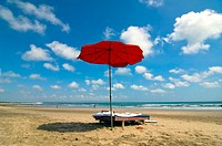 Seminyak Beach, red sunshade on beach, sky with puffy clouds. Seminyak. Bali. Indonesia