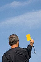 football referee holding up yellow card