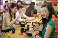 Young women eating noodles in restaurant