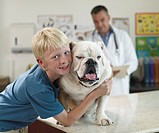 Boy Hugging Dog in Veterinarian´s Office