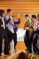 Businesspeople Dancing on Table