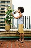 Man on Balcony Watering Plant
