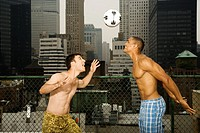 Two Young Men Playing Soccer on Rooftop