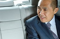 Businessman sitting in backseat