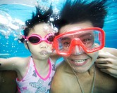 Father and Daughter Swimming Underwater