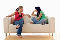 Two Teenage Girls Relaxing on Sofa