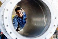 Factory Worker Looking Through Pipe