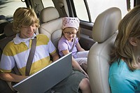 Boy Using Laptop in Back Seat of Car