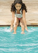 Girl sitting on edge of pool with hands and feet in water