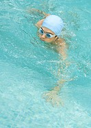 Person in swimming pool wearing bathing cap and goggles