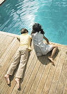 Boy and girl sitting at edge of swimming pool, high angle view