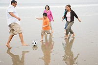 Family Playing with Soccer Ball on Beach