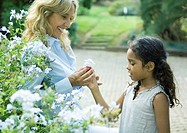 Mature woman handing granddaughter flower