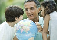 Mature man looking at globe with grandchildren