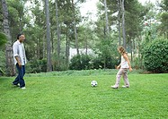 Mature man playing soccer with granddaughter
