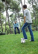 Mature man and teenage boy playing soccer