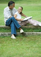 Mature man reading with granddaughter outdoors
