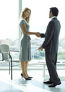 Businessman shaking hands with woman in lobby
