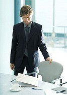 Businessman pulling seat out in office