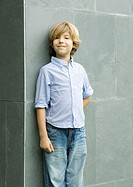 Boy leaning against wall, smiling, portrait