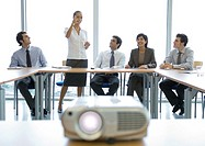 Business colleagues having meeting, videoprojector in foreground