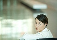 Woman, looking over shoulder at camera