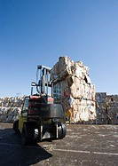 Forklift carrying bales of used paper