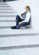Businessman sitting on steps, smiling