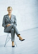 Businesswoman sitting in chair, full length