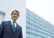 Businessman, portrait, standing in front of office building