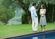 Man and woman standing near edge of pool with documents and cell phone