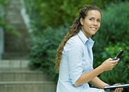 Woman using cell phone outdoors, holding agenda
